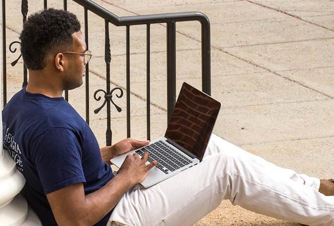adult student on laptop leaning against a column