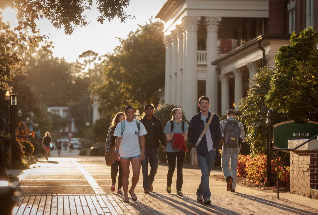 Students walking on Front Campus as the sun sets