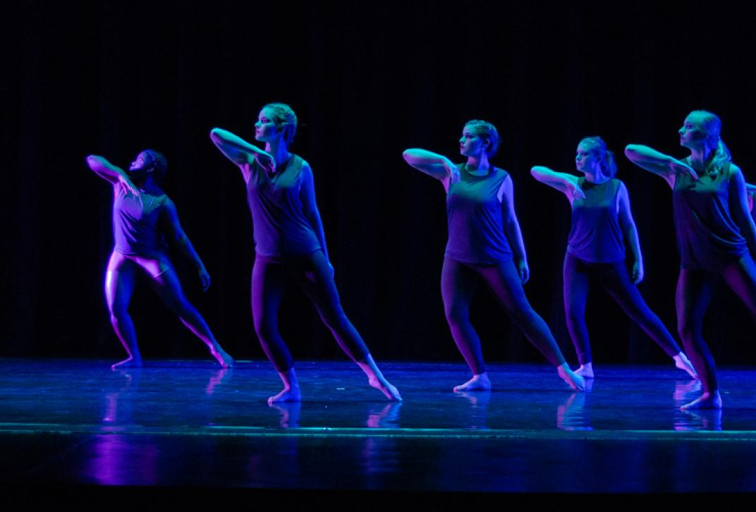 dancers in formation on dark stage