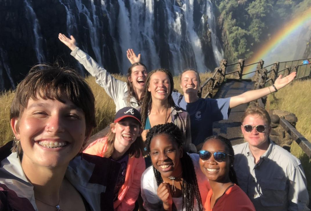 Students Taking Selfie in Front of Waterfall and Rainbow.