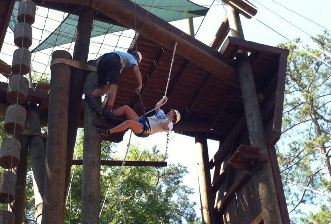 students climb ropes course