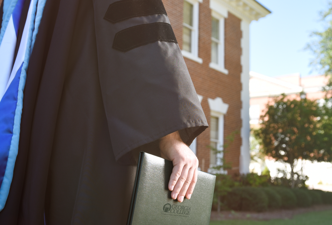 An anonymous graduate holds a diploma cover.