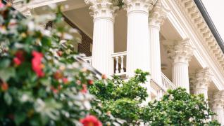 view of ornate columns on building and rose bushes