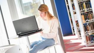 student on laptop in library near window