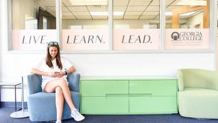 student in chair with live, learn, lead banner