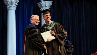 student receiving diploma from dean