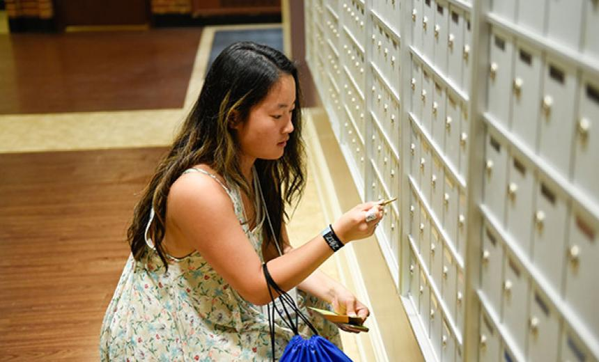 student checking for mail in mailroom
