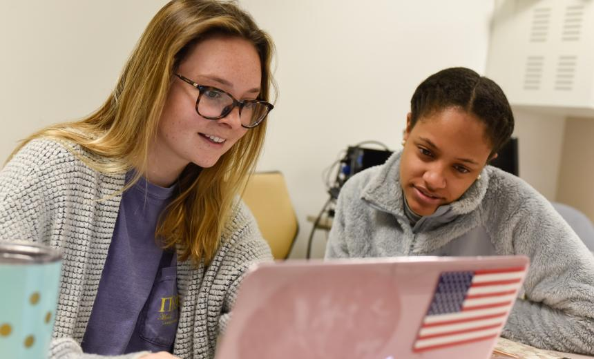 two female students look at a compute