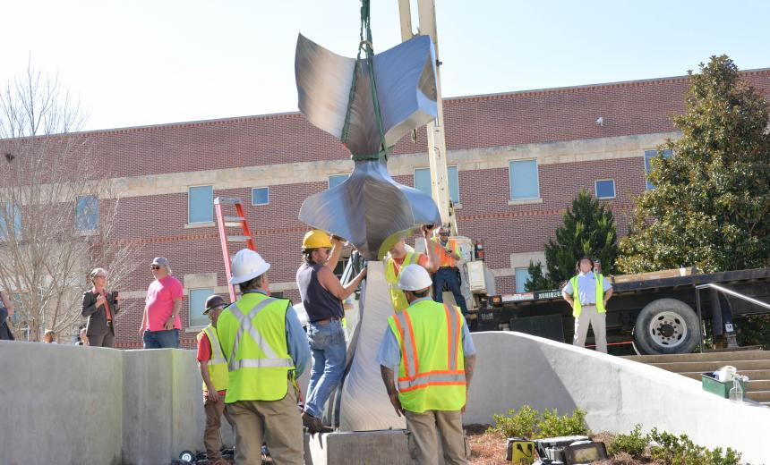 workers raising a sculpture