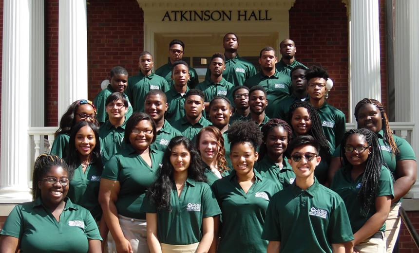 minority youth business group posing for photo on steps of Atkinson Hall