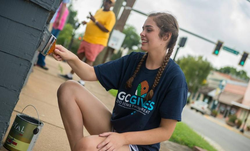 student painting a building on gc gives day