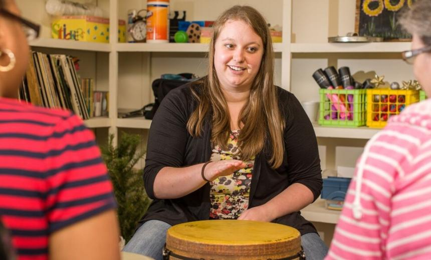 student using drum in group therapy