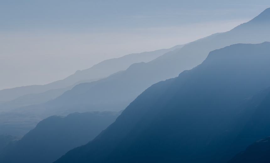Four blue-colored mountain ridges receding into the fog.