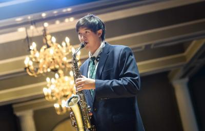 student playing saxophone in ballroom