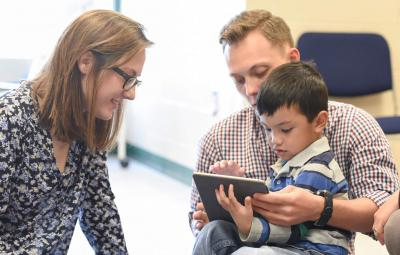 students working with child on ipad
