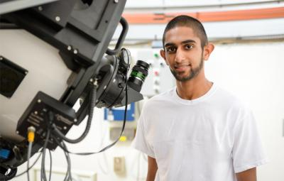 student standing at telescope