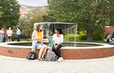students sitting on fountain