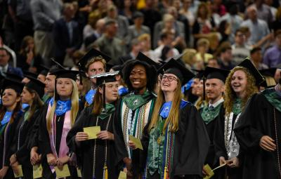 Graduates smile at each other during the May 2019 ceremony.