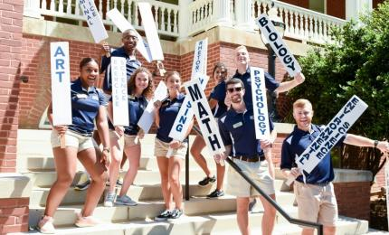 orientation team holds up signs for each program