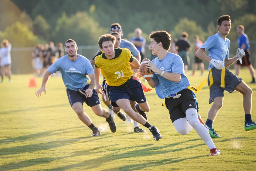 male students play flag football
