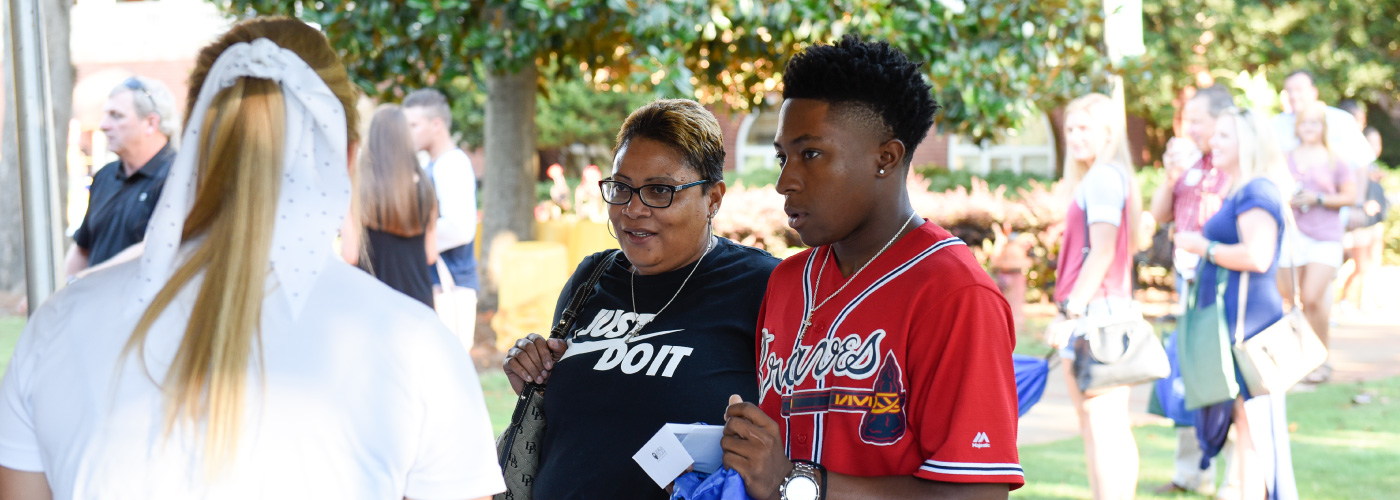 A student and mom check-in for Orientation with an Admissions counselor