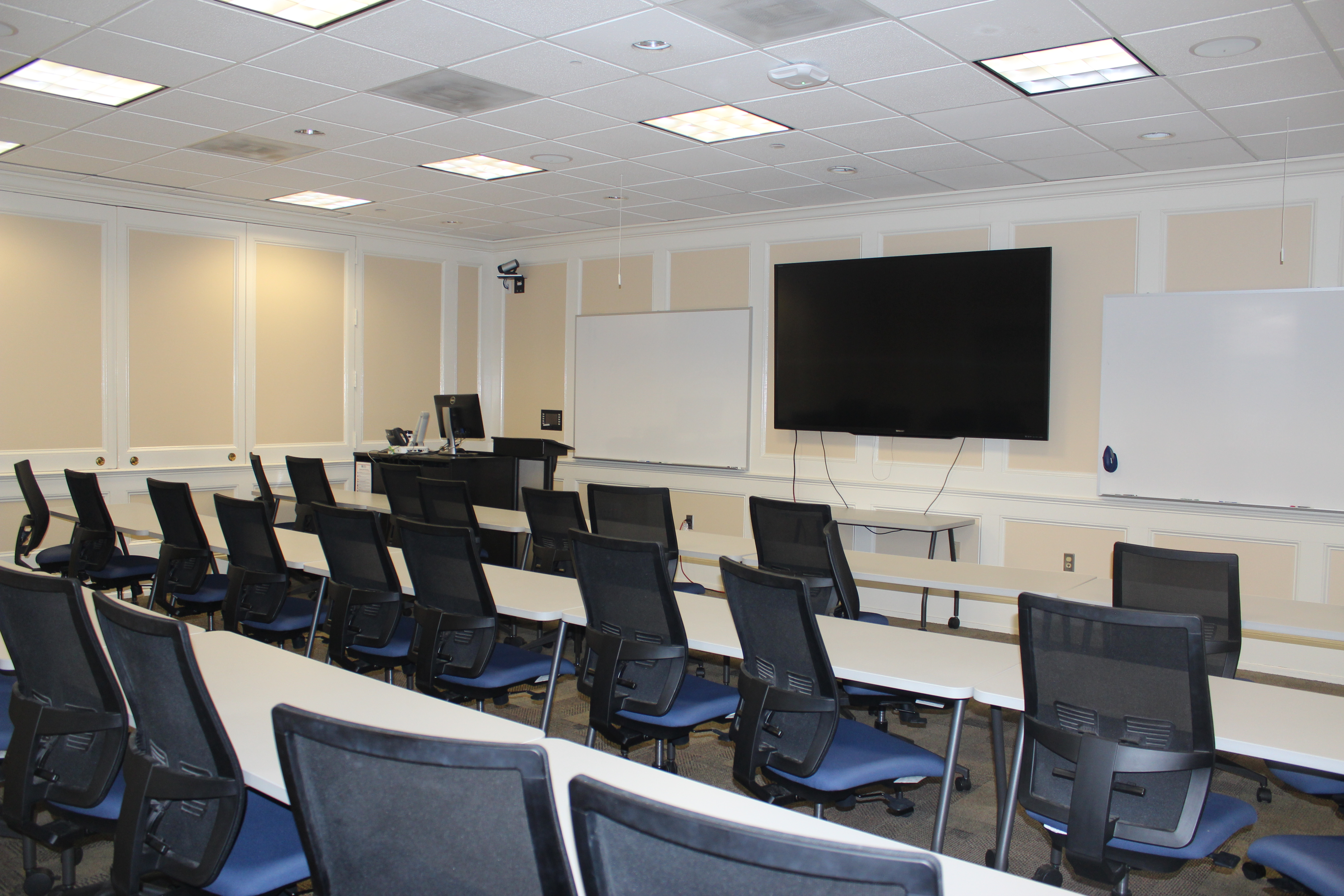 Atkinson 110 classroom showing tables, chairs and front of the room displays