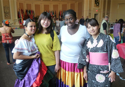 Photo of four smiling students at the International Dinner posing in traditional clothing representative of their home nations.