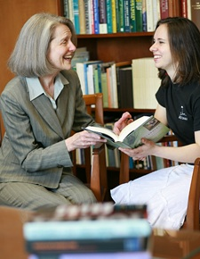 Dr. Whitaker and student laughing and reading the contents of an open book.